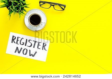 Membership concept. Template for registration. Register now hand lettering iconon word desk with glasses, coffee, plant on yellow background top view. stock photo