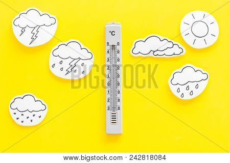 Weather forecast concept. Air temperature. Termometer among cloud and lightening, sun, rainy clouds on yellow background top view. stock photo