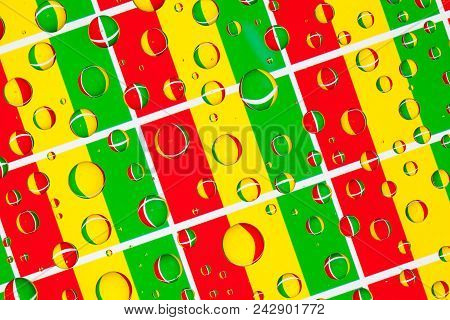 Flags  of Guinea, behind a glass covered with rain drops.Pattern from Guinean flags stock photo