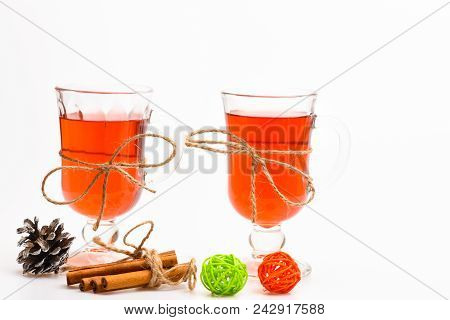 Hot drinks concept. Glasses with mulled wine or cider tied with twine string on white background. Traditional mulled wine with spices. Mulled wine or hot beverage in glasses and cinnamon sticks. stock photo