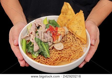 Chinese food ,Crispy noodle and crisy wonton in Chinese kale soup with softed pork , fried softed tofu ,carrot,mushroom and red chili . stock photo