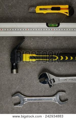 spirit level, hammer, adjustable wrench ans spanner on gray surface stock photo