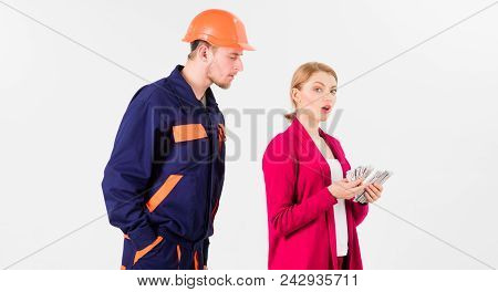 Builder in helmet looks at woman with busy face counting money, isolated on white background. Repairer, builder wants salary for work. Payment concept. Customer deceives repairman, builder, mechanic. stock photo