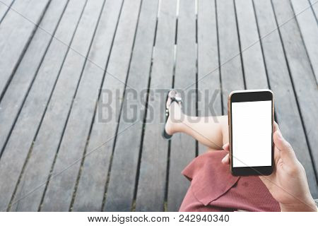 Close up man hand holding black smartphone on beautiful calm blue sea and sandy beach background. Male hand using mobile phone in outdoor summer beach in holiday vacation to taking picture. stock photo