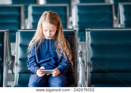 Adorable little girl in airport in waiting room stock photo