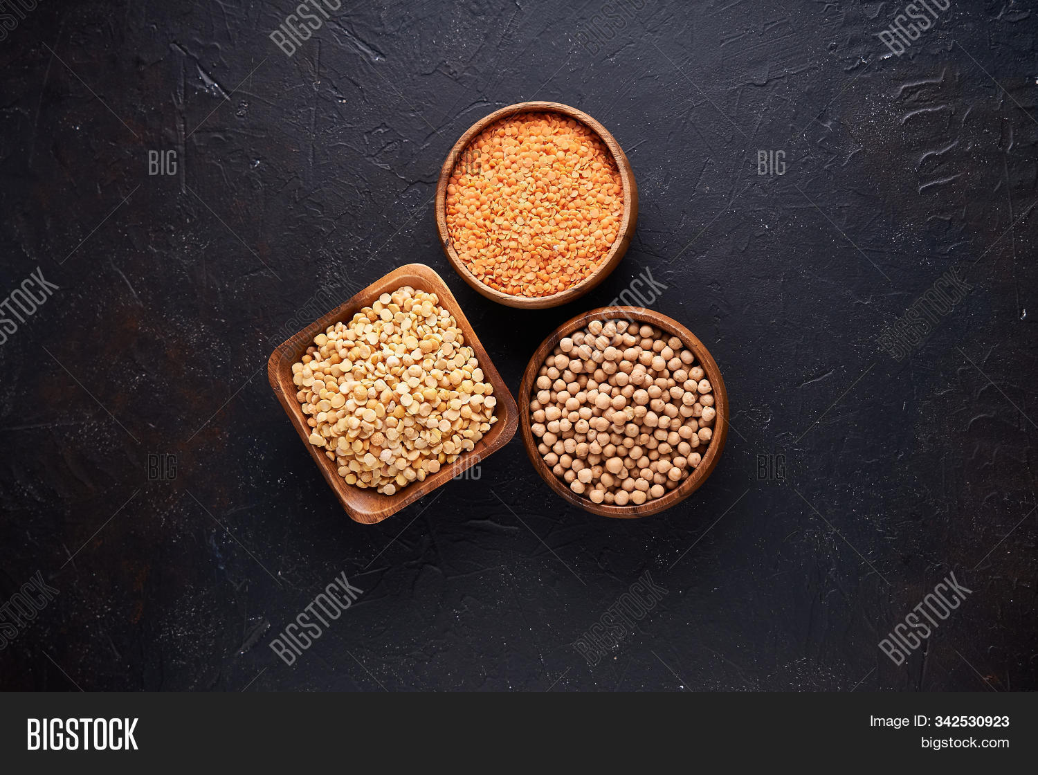Assortment of cereals, legumes, cereals, grains, lentils, chickpeas, peas, beans in wooden bowls on a dark background