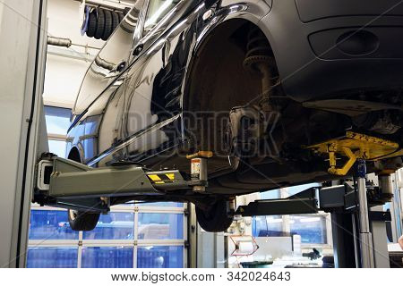 A car at a service station is raised on a lift for repair. The front wheel is removed on the car, the elements of the front suspension are visible. Concept service and car repair at a service station. stock photo