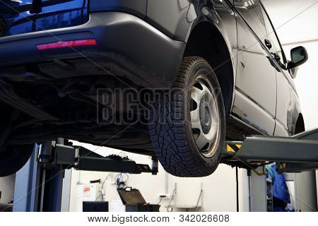 A commercial vehicle (minivan) at a service station is lifted on a lift for repair, tire fitting. Car service interior in the background is blurred. Concept service and car repair at a service station stock photo