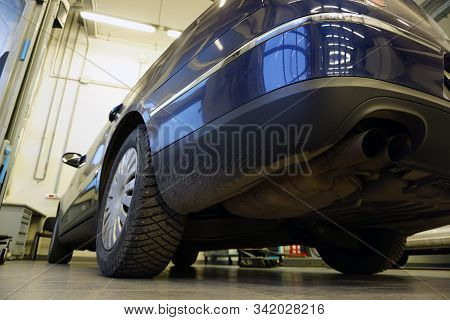 Blue luxury car at a service station, bottom rear view. Concept service and car repair at a service station. Car service interior in the background is blurred. stock photo