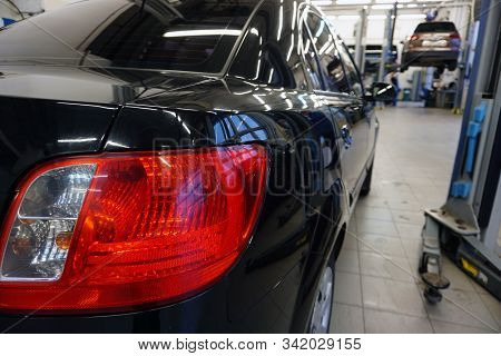 The black car at the service station is prepared for repair. Close-up of a red taillight, in the background the interior of a car service is blurred. Concept service and car repair at a service. stock photo