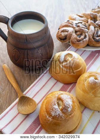 On the towel are fresh soft buns and a wooden spoon. A large mug of milk on the table. Background with delicious sweet baking and milk. stock photo