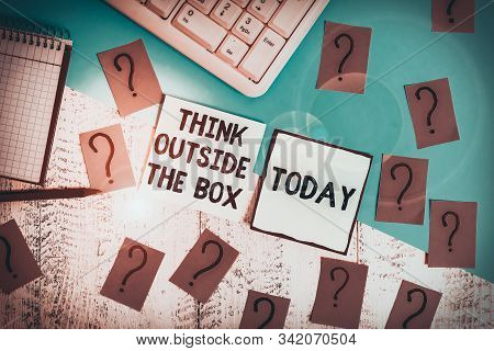 Conceptual hand writing showing Think Outside The Box. Business photo showcasing Be unique different ideas bring brainstorming Writing tools and scribbled paper on top of the wooden table. stock photo