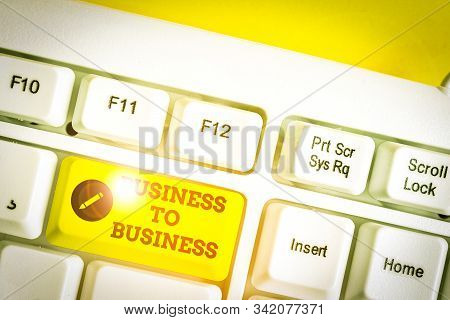 Conceptual hand writing showing Business To Business. Business photo showcasing Commercial Transaction between two Businesses White pc keyboard with note paper above the white background. stock photo