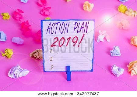 Handwriting text Action Plan 2019. Concept meaning proposed strategy or course of actions for current year Colored crumpled papers empty reminder pink floor background clothespin. stock photo
