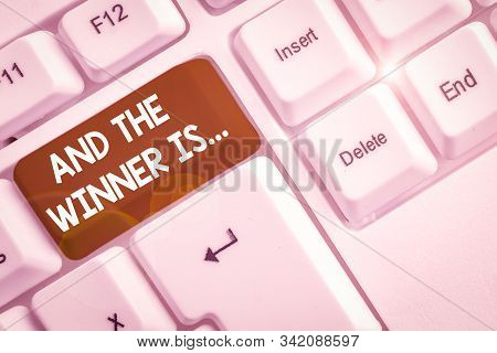 Writing note showing And The Winner Is. Business photo showcasing announcing a demonstrating or thing that wins something White pc keyboard with note paper above the white background. stock photo