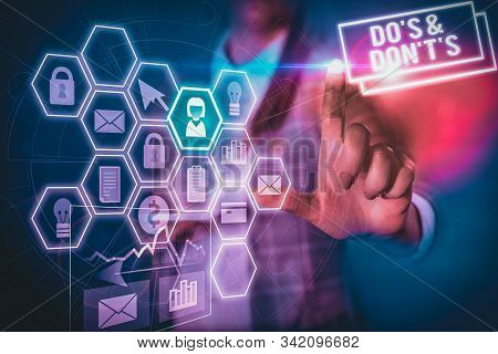 Conceptual hand writing showing Do S And Don T S. Business photo text Confusion in one s is mind about something Woman wear formal work suit present using smart latest device. stock photo