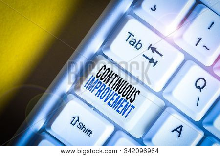 Writing note showing Continuous Improvement. Business photo showcasing ongoing effort to improve products or processes White pc keyboard with note paper above the white background. stock photo