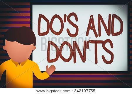 Text sign showing Do S And Don tS. Conceptual photo Rules or customs concerning some activity or actions Young man standing in front whiteboard pointing to project. photo Art. stock photo