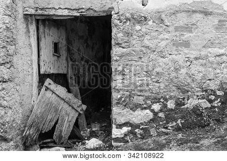 Broken door at the entrance of an abandoned house. stock photo