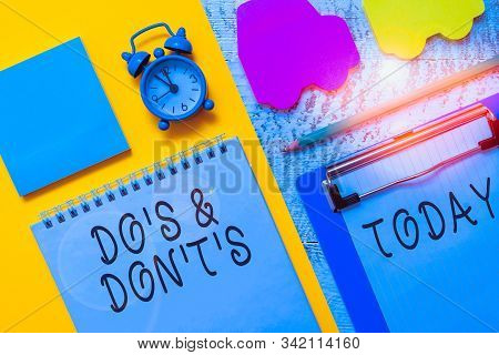 Writing note showing Do S And Don T S. Business photo showcasing Confusion in one s is mind about something Notepad clipboard sheet marker car sticks alarm clock wooden background. stock photo