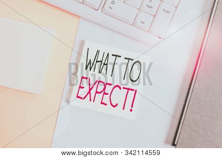 Text sign showing What To Expect. Conceptual photo asking about regard something as likely to happen occur Empty blank paper with copy space and pc keyboard above orange background table. stock photo