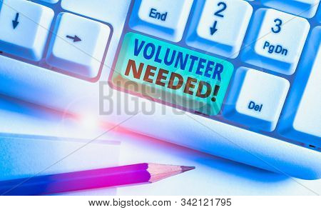 Writing note showing Volunteer Needed. Business photo showcasing asking demonstrating to work for organization without being paid White pc keyboard with note paper above the white background. stock photo