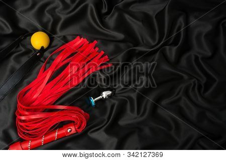 Red whip, gag, anal plug on a black silk background. Accessories for adult sexual games. Toys for BDSM stock photo
