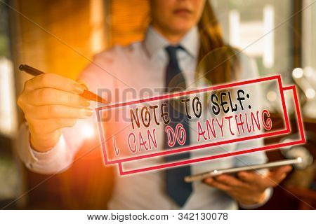 Text sign showing Note To Self I Can Do Anything. Conceptual photo Motivation for doing something confidence Blurred woman in the background pointing with finger in empty space. stock photo