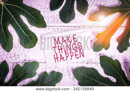 Word writing text Make Things Happen. Business concept for Exert Effort to Achieve and Fulfill something Go and Act Leaves surrounding notepaper above a classic wooden table as the background. stock photo