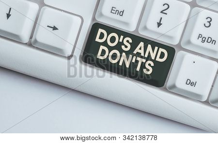 Conceptual hand writing showing Do S And Don tS. Business photo showcasing Rules or customs concerning some activity or actions White pc keyboard with note paper above the white background. stock photo