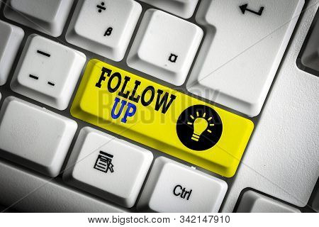 Text sign showing Follow Up. Conceptual photo a continuation of something that has already been started White pc keyboard with empty note paper above white background key copy space. stock photo