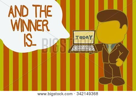 Writing note showing And The Winner Is. Business photo showcasing announcing a demonstrating or thing that wins something Standing professional businessman holding open laptop right hand side. stock photo