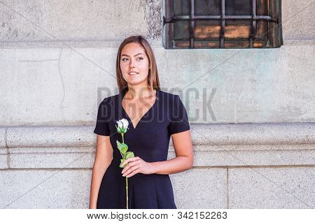 I love you, waiting for you. Young East European Woman with long brown hair, wearing black short sleeve, v neck dress, holding white rose flower, standing by wall on street in New York City, thinking. stock photo
