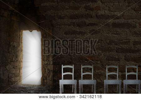 Chairs for waiting. Mystical passage to eternity. Collage concept. Ancient masonry in a dark room with a luminous opening. stock photo