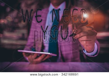 Writing note showing We Need You. Business photo showcasing to fulfill the needs of the assignment duty or obligation Female business person sitting by table holding mobile phone. stock photo