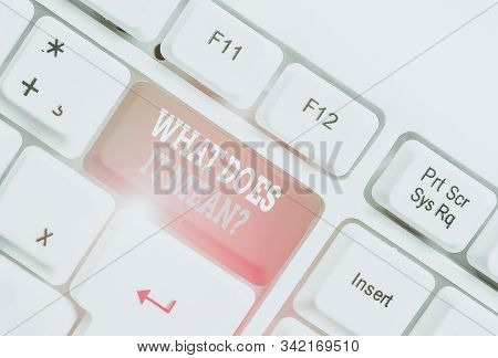 Writing note showing What Does It Mean Question. Business photo showcasing Give me the meaning of something Definition White pc keyboard with note paper above the white background. stock photo
