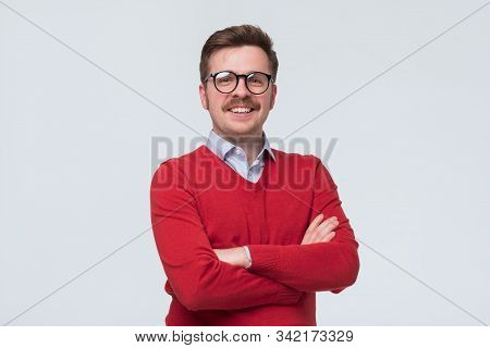man in red sweater and glasses standing in front of camera, feeling positive, confident stock photo
