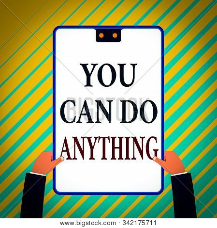 Writing note showing You Can Do Anything. Business photo showcasing Motivation for doing something Believe in yourself White rectangle clipboard with blue frame has two holes holds by hands. stock photo