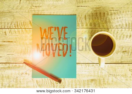 Writing note showing We Ve Moved. Business photo showcasing having strong feelings sadness or sympathy has said or done Stationary placed next to a cup of black coffee above the wooden table. stock photo