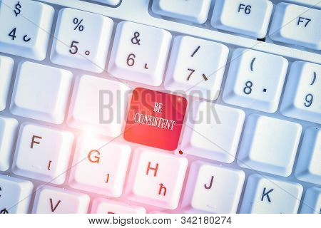 Text sign showing Be Consistent. Conceptual photo Uniform Persistent Firm Unalterable Even Unchanging Rapport White pc keyboard with empty note paper above white background key copy space. stock photo