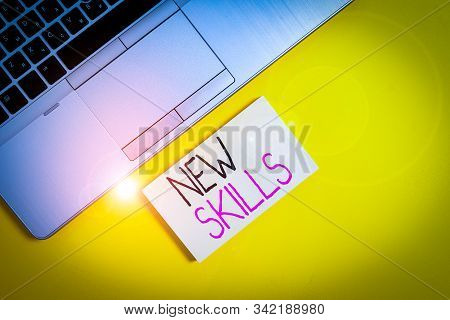 Word writing text New Skills. Business concept for Recently Acquired Learned Abilities Knowledge Competences Slim trendy silver open laptop square sticky notepad colored background. stock photo