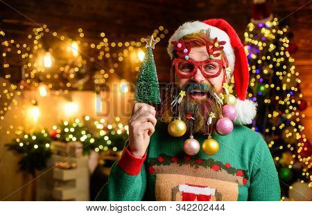 Christmas tree. Merry Christmas and happy new year. Bearded Santa Claus in party glasses holds small Christmas tree. Christmas beard style. Happy Santa with decoration balls in beard holds fir-tree stock photo