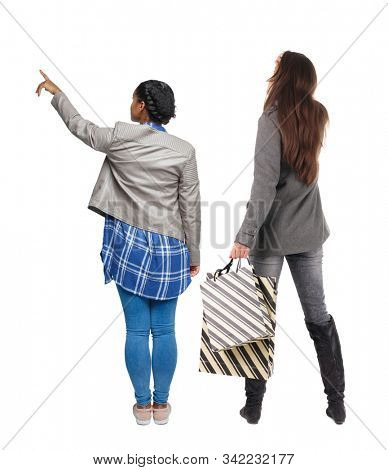 back view of two women with shopping bags  in winter jacket. backside view of person. Rear view people collection. Isolated over white background. Two girls with bags stand next procurement. stock photo