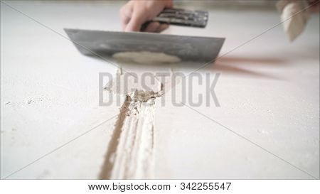 Worker aligns the wall with a spatula. Worker aligns the wall with construction putty. a close shot at the builder hands, who level the wall with a long spatula and plaster, the man applies the composition on the surface stock photo