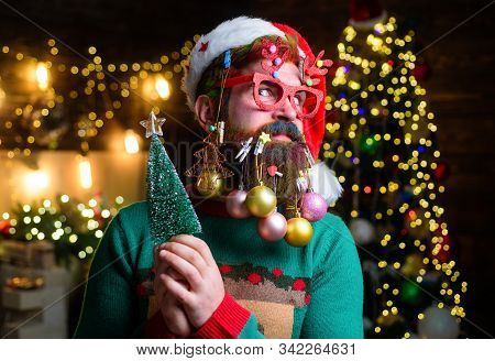 Surprised Santa with New Year balls in beard holds fir-tree. Christmas beard style. Christmas tree. Merry Christmas and happy new year. Bearded Santa Claus in party glasses holds small Christmas tree stock photo