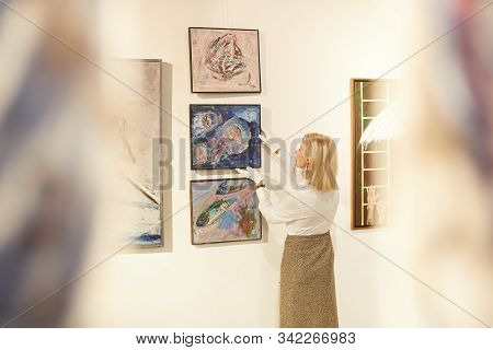 Back view portrait of female art expert hanging paintings while working in art gallery or museum, copy space stock photo