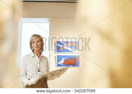Waist up portrait of elegant mature woman holding painting and looking at camera while working in art gallery or museum, copy space stock photo