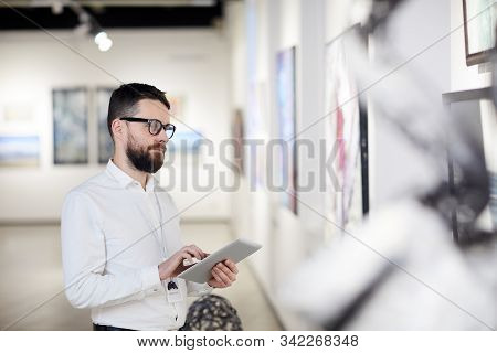 Waist up portrait of bearded art gallery manager using digital tablet while organizing exhibition in museum, copy space stock photo