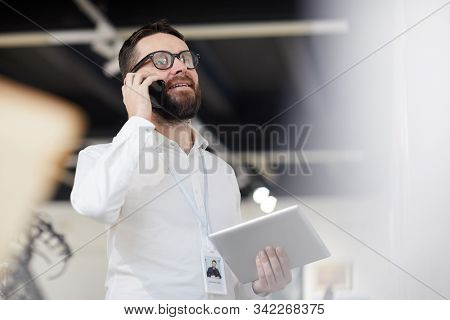 Low angle portrait of bearded art gallery manager speaking by phone while organizing exhibition in museum, copy space stock photo