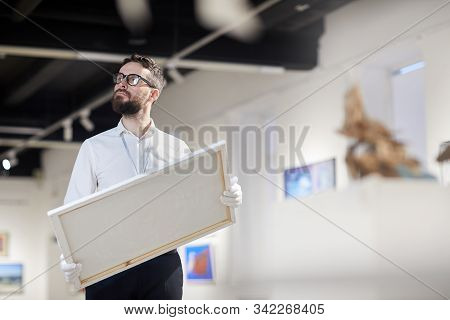 Waist up portrait of bearded art gallery worker holding painting while organizing exhibition in museum, copy space stock photo
